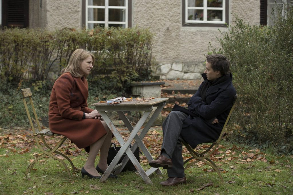 Lara draußen an einem Holztisch im Gespräch mit ihrem Sohn Victor