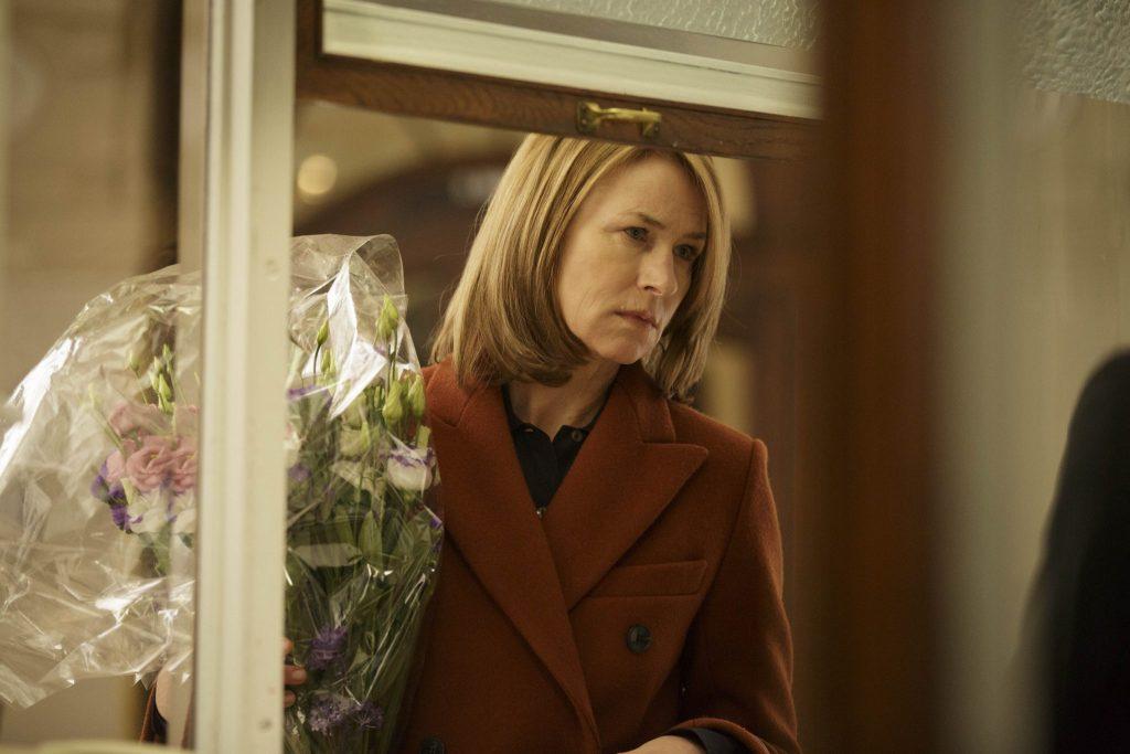 Lara an einem Ticketschalter, in der Hand ein Blumenstrauß