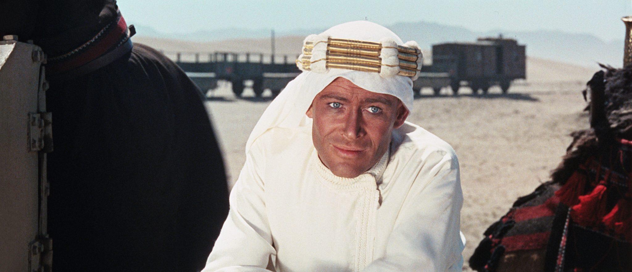 Lawrence von Arabien (Peter O'Toole) sitzt in einem edlen, weißen Beduinen-Gewand mitten in der Wüste und guckt verschmitzt. Im Hintergrund fährt ein Zug vorbei, die er mit den arabischen Stämmen regelmäßig überfällt.