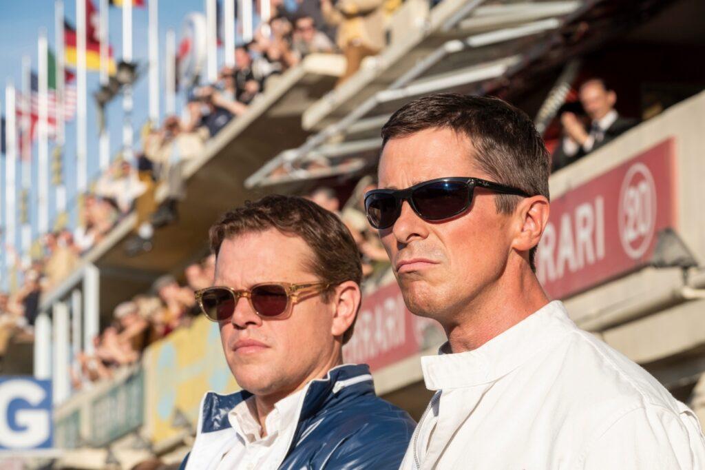 """Der deutsche Filmtitel """"Le Mans 66: Gegen jede Chance"""" unterscheidet sich enorm vom originalen Filmtitel """"Ford v Ferrari"""". Auf dem Bild sind Matt Damon und Christian Bale zu sehen. Beide stehen nebeneinander und schauen für den Betrachter nach links. Sie stehen vor einer vollbesuchten Tribüne und tragen Sonnenbrillen."""