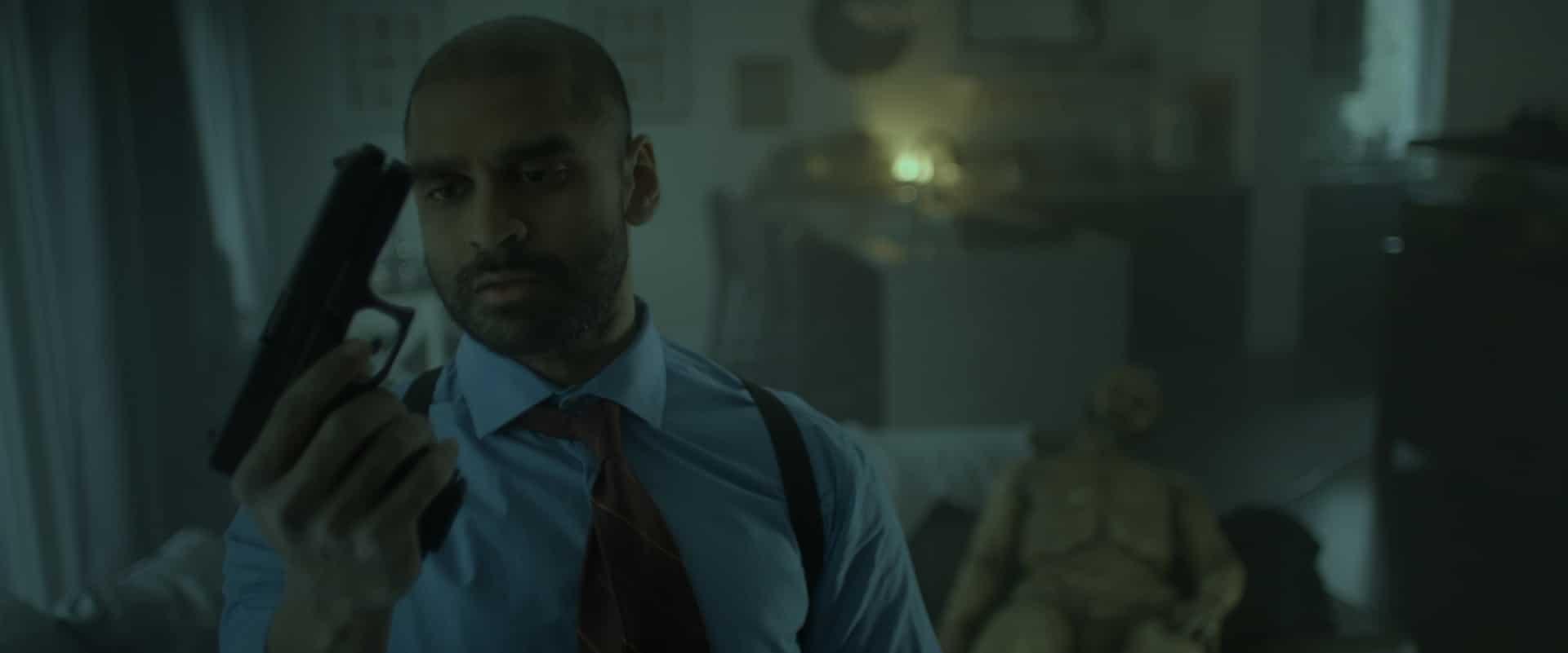 Drew, die Hauptfigur aus Lifechanger, steckt nun im Körper eines schwarzen Polizisten mit Hemd, Krawatte und Kurzhaarfrisur. Er mustert eine Pistole in seiner Hand, im Hintergrund ist ein Wohnzimmer mit Möbeln zu sehen. Auf dem Sofa sitzt ein nackter, ausgezerrter Körper.