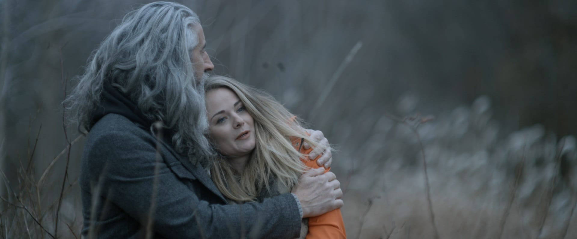Drew, die Hauptfigur aus Lifechanger, ist nun ein Mann mittleren Alters mit langen grauen Haaren und Bart. Er sitzt gemeinsam mit seiner Freundin Julia in einer Wiese, sie lehnt ihren Kopf sanft an seine Schulter.