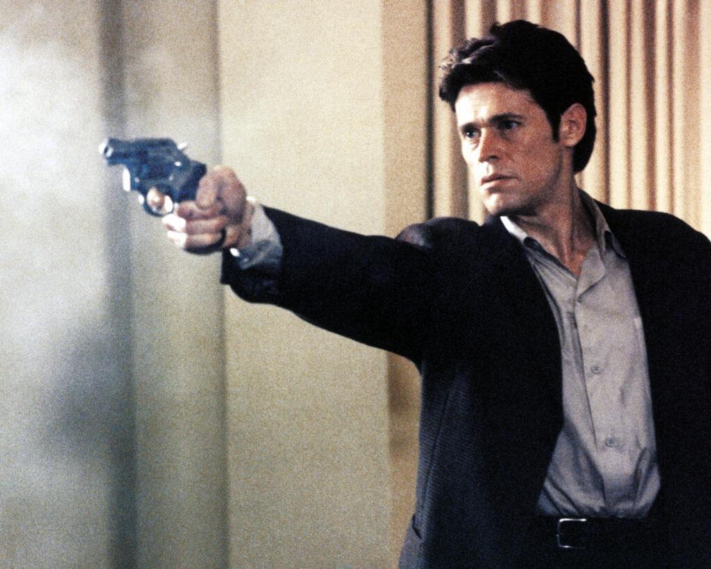 Willem Dafoe zielt und schießt mit einem Revolver - Light Sleeper.