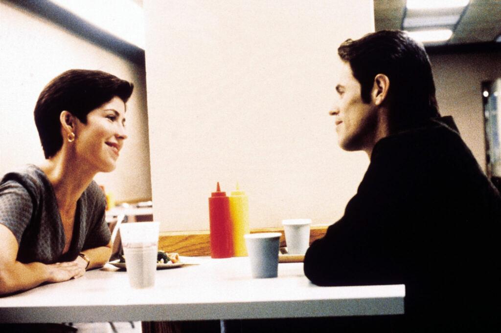 Dana Delaney und Willem Dafoe sitzen sich an einem Tisch gegenüber und lächeln sich an - Light Sleeper.