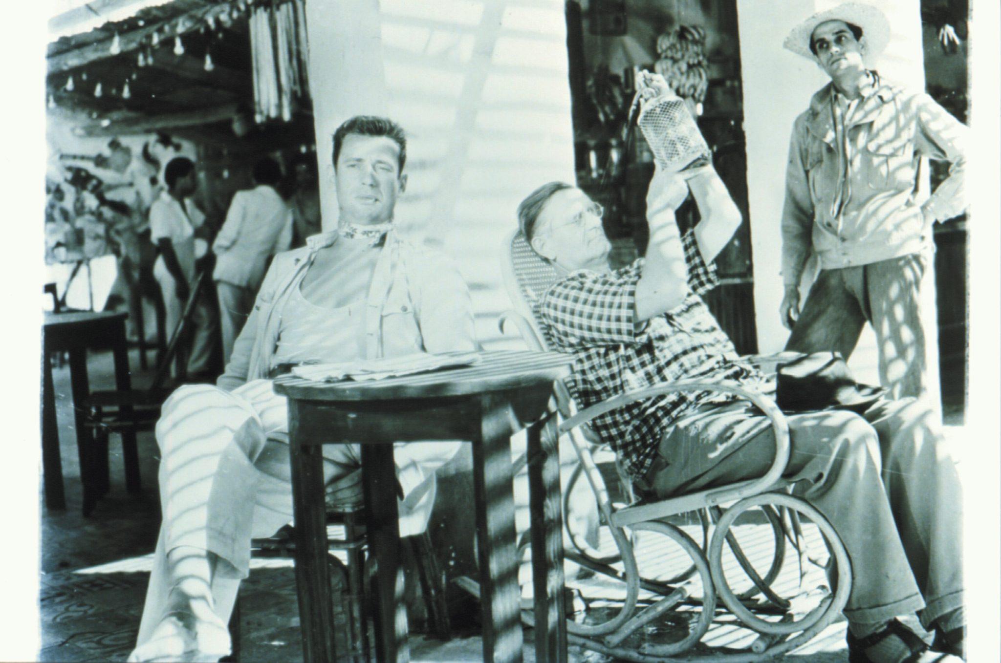 Yves Montand als Mario sitzt zusammen mit einem älteren Herren an einem Tisch in der Sonne in Lohn der Angst.