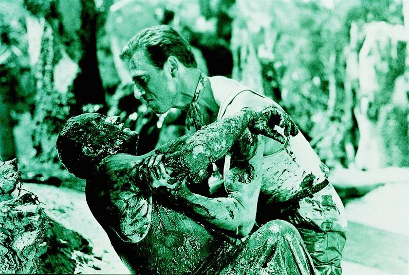 Der mit Erdöl beschmierte Charles Vanel als Jo wird von Yves Montand als Mario in den Händen gehalten in Lohn der Angst.