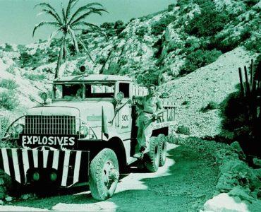 """Ein Wagen mit der Aufschrift """"Explosives"""" hält in """"Lohn der Angst"""" auf einer Straße, die zwischen hohen Hügel entlang führt. Charles Vanel als Jo sitzt am Steuer und Yves Montand als Mario lehnt an der Beifahrerseite."""