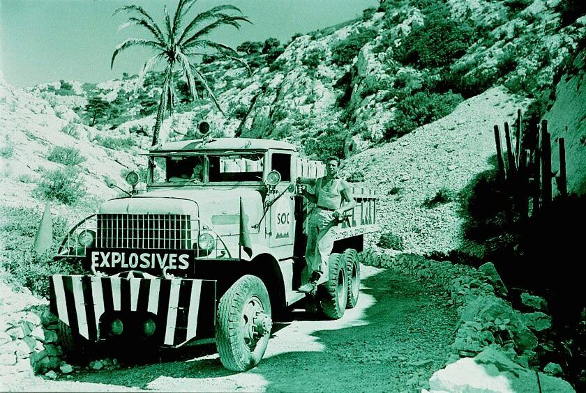 """Ein Wagen mit der Aufschrift """"Explosives"""" hält in Lohn der Angst auf einer Straße, die zwischen hohen Hügeln entlang führt. Charles Vanel als Jo sitzt am Steuer und Yves Montand als Mario lehnt von außen an der Beifahrerseite."""
