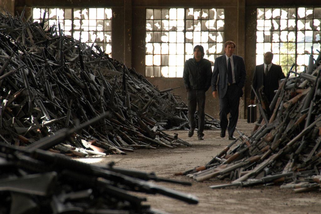 Auf dem Bild gehen Yuri, Vitaly (Jared Leto) und noch ein weiter Mann durch eine Halle, in der sich bergeweise Maschinengewehre stapeln. Diese liegen durcheinander auf mehrere Haufen zwischen denen die drei Männer durchmaschieren. - Lord of War