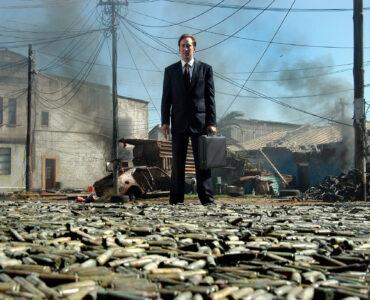 Auf dem Bild ist Nicolas Cage zu sehen, der in irgendeinem Krieggebiet zu stehen scheint. Der Boden auf dem er recht gelassen steht, ist übersät mit Patronenhülsen. - Lord of War