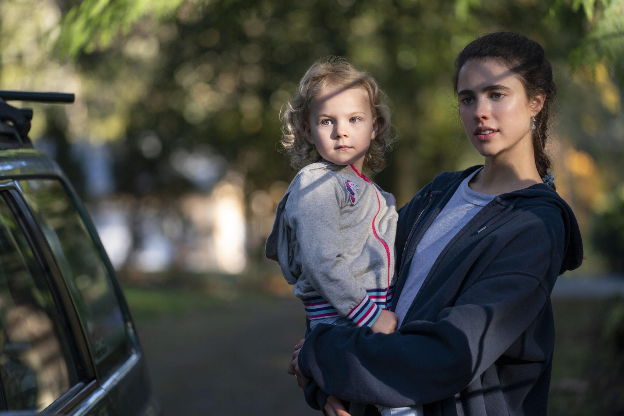Margaret Qualley hält ein kleines Mädchen mit blonden Haaren in den Armen. Sie stehen vor einem Auto.
