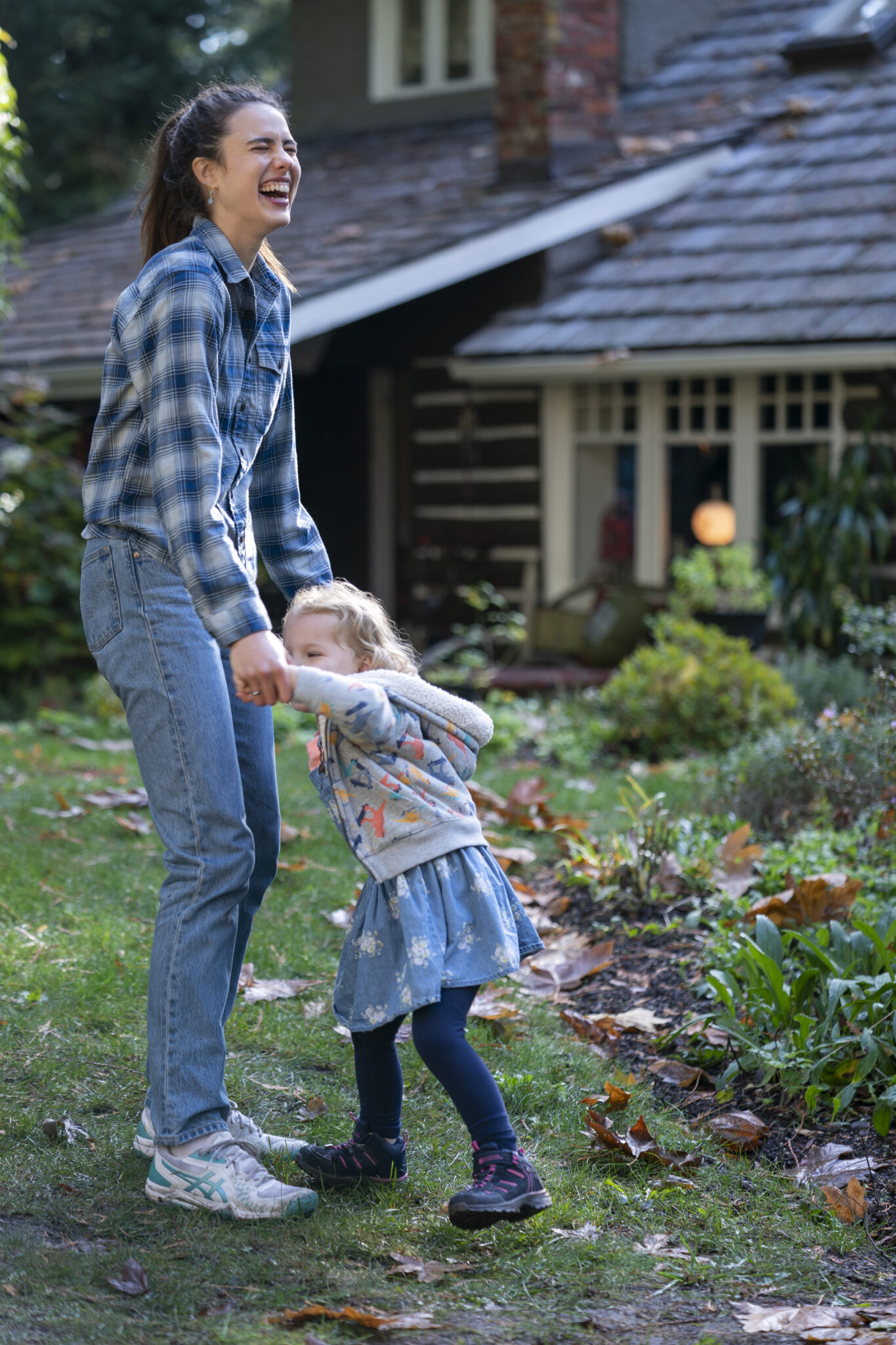 Margaret Qualley in Jeans und Karohemd mit lachendem Gesicht mit einem kleinen Mädchen Hand in Hand vor einem Haus im Garten.