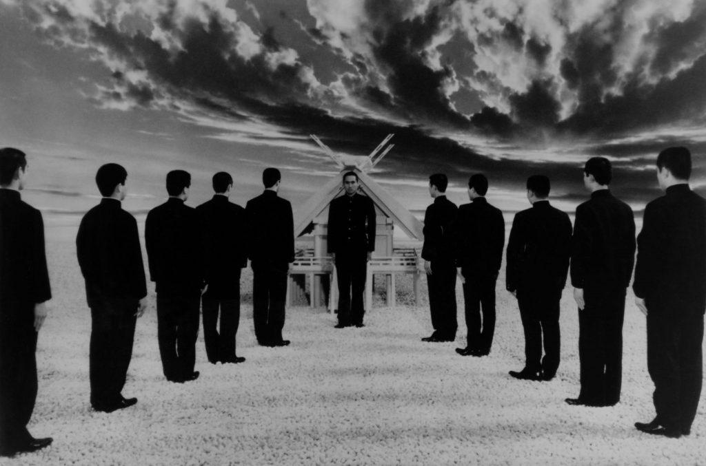 In einem Ausschnitt aus dem dritten Kapitel stehen zwei Reihen junger Männer vor einem Mann in Uniform, im Hintergrund ein Wolkenhimmel