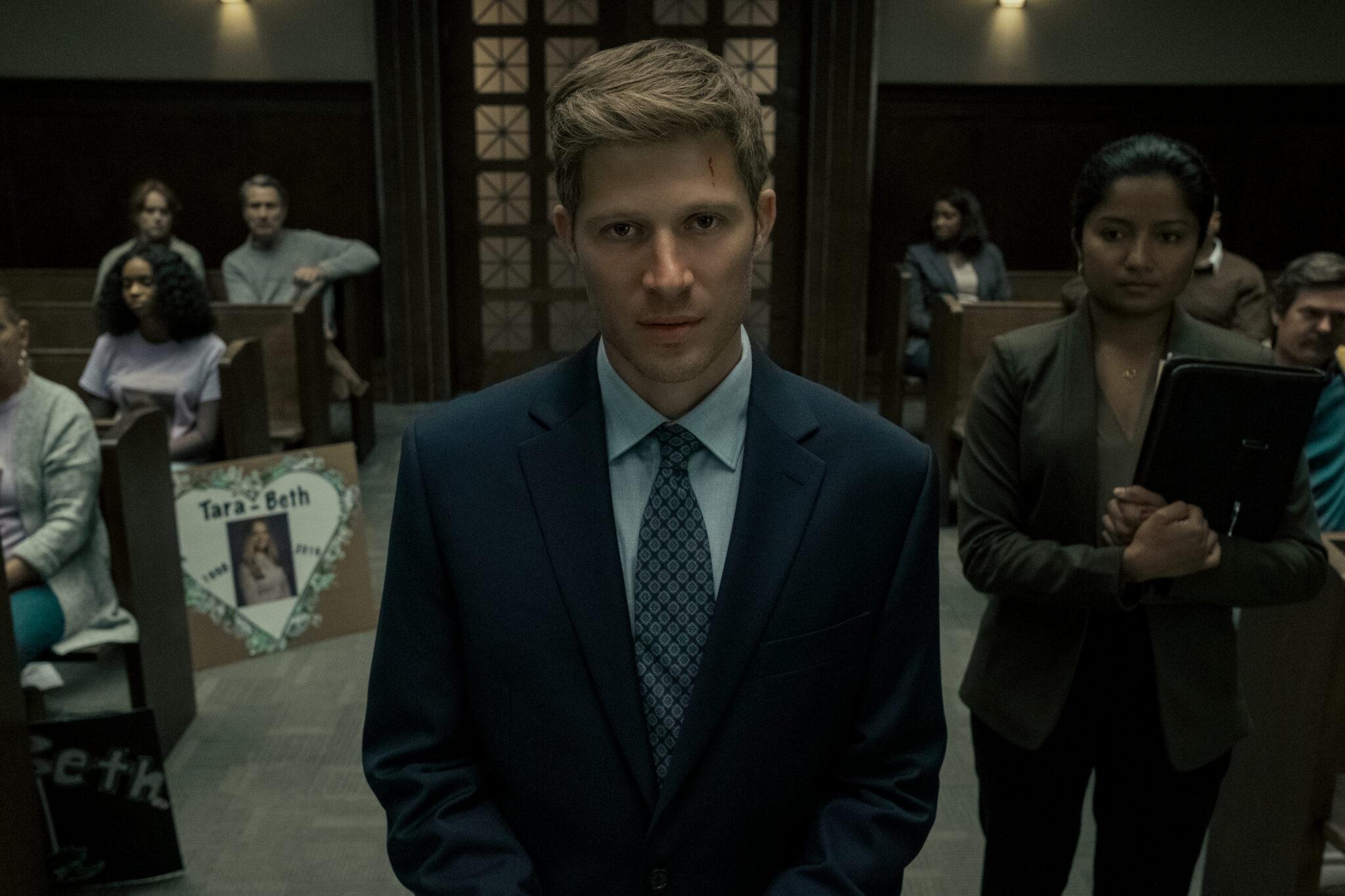 Riley Flynn (Zach Gilford) im Anzug in einem Gerichtsaal mit stoischem Gesichtsausdruck. Hinter ihm sieht man zahlreiche Personen in den Sitzreihen und rechts neben ihm eine junge Frau, die eine Mappe vor ihrer Brust hält - Midnight Mass