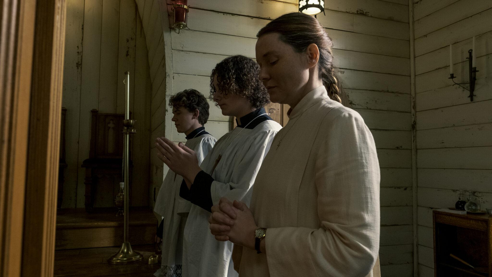 Man sieht drei weißbekleidete Messdiener mit betender Handhaltung vor einer weißen Holzwand; zwei sind junge Männer, eine ist eine erwachsene Frau - Midnight Mass
