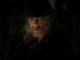 Joe Collies Gesicht komplett vor schwarzem Hintergrund und nur erleuchtet vom Feuerzeug der Zigarette, die er sich gerade entzündet.