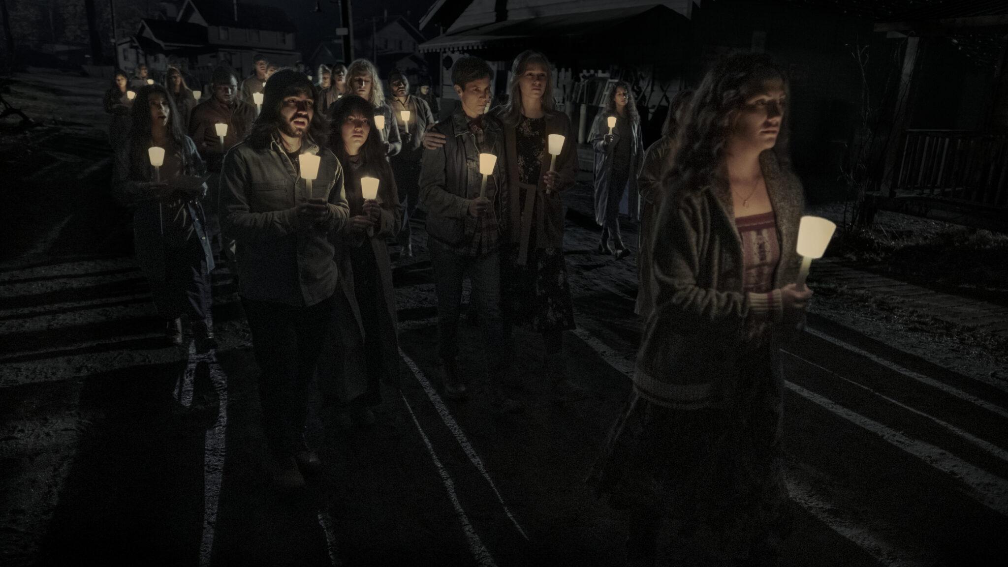 Eine Gruppe Personen im Dunkeln mit Kerzenleuchtern