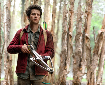 Joel Dawson (Dylan O'Brien) steht mit einer Armbrust vor einigen rinderlosen Baumstämmen. Er trägt einen roten Hoodie und darunter ein grünes Shirt.