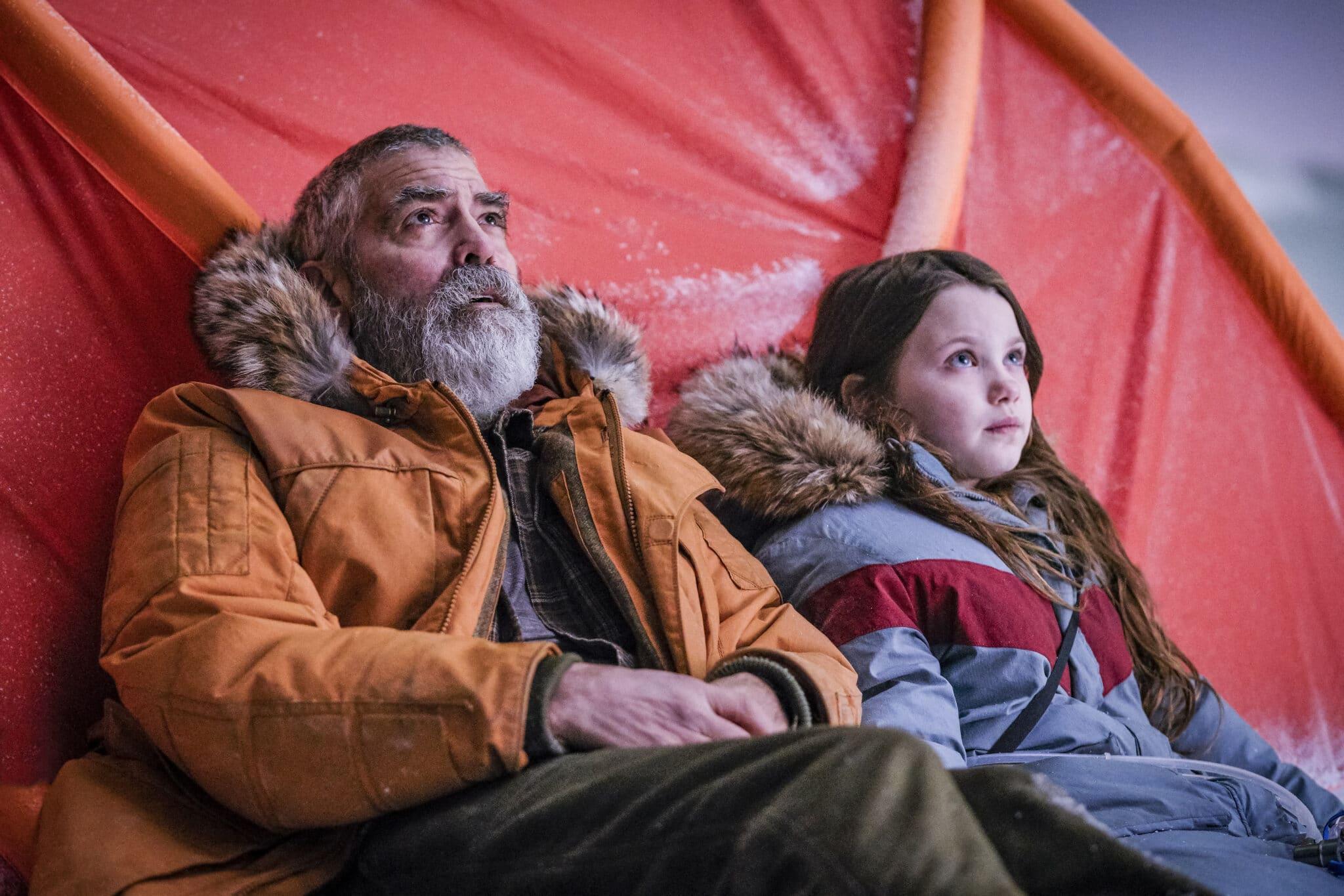 Augustin (George Clooney) und Iris sitzen in ihren Winterparkas vor einem roten Zelt und blicken in Richtung des Himmels.