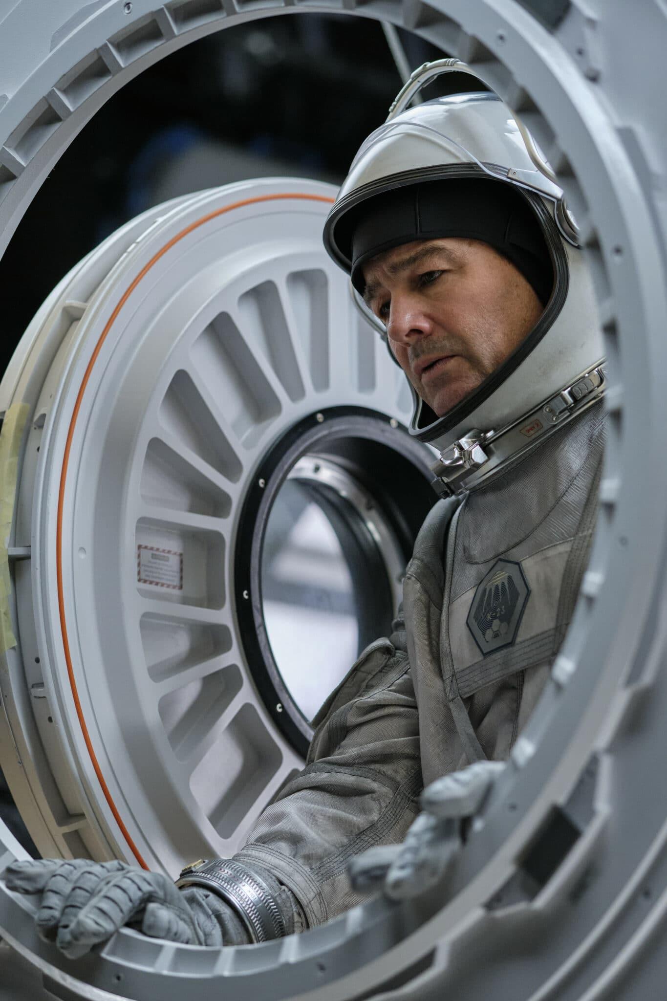 Dr. Mitchell (Kyle Chandler) steht im offenen, weißen Raumanzug mit nachdenklicher Miene vor einer geöffneten Luke.