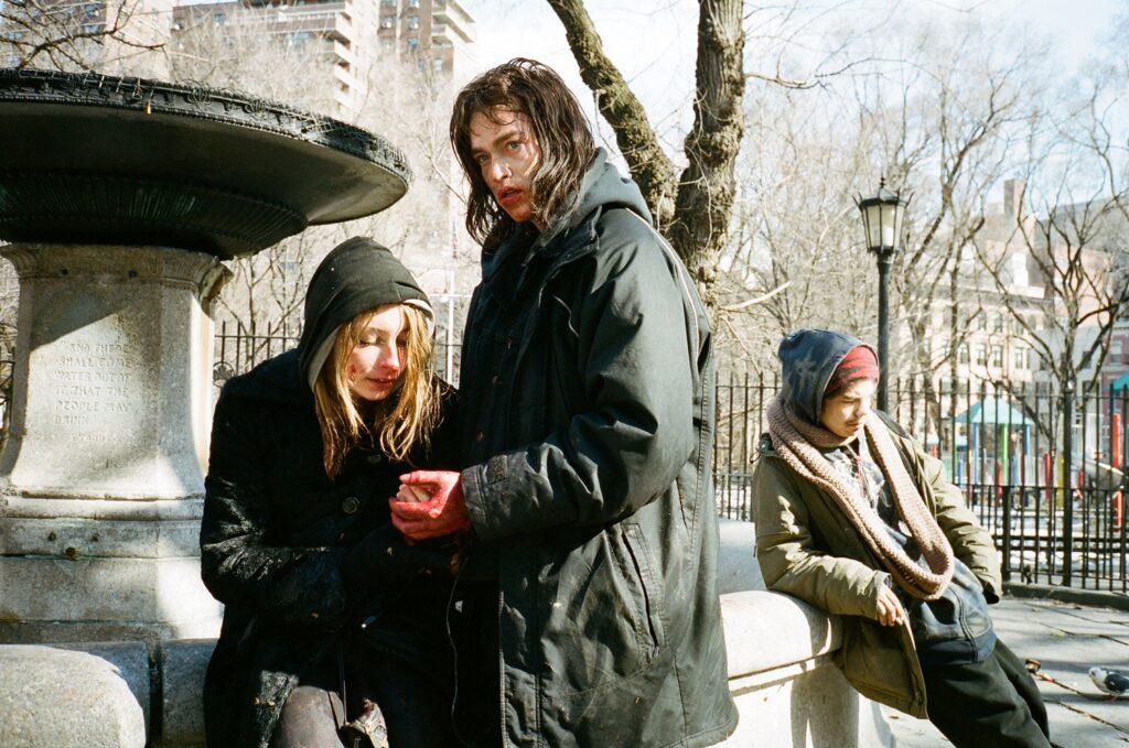 Vor einer Statue sitzen Harley (Arielle Holmes) und Ilya (Caleb Landry Jones), der ihre verletzte Hand hält. Im Hintergrund befindet sich Evan (Manny Aguila), ein weiterer Süchtiger. © Koch Films