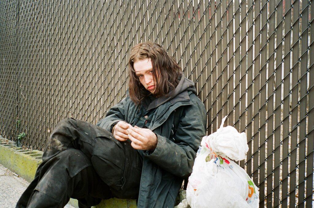 Ilya (Caleb Landry Jones) dreht sich gerade eine Zigarette, während er an einem Zaun sitzt. Neben ihm liegt ein prall gefüllter Plastiksack. © Koch Films