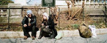 Mike (Buddy Duress) und Harley (Arielle Holmes) sitzen rauchend am Straßenrand. Rechts neben ihnen liegt der Rucksack von Harley und einige Plastiktüten. Im Hintergrund befindet sich das Soldiers' and Sailors' Monument in New York. © Koch Films