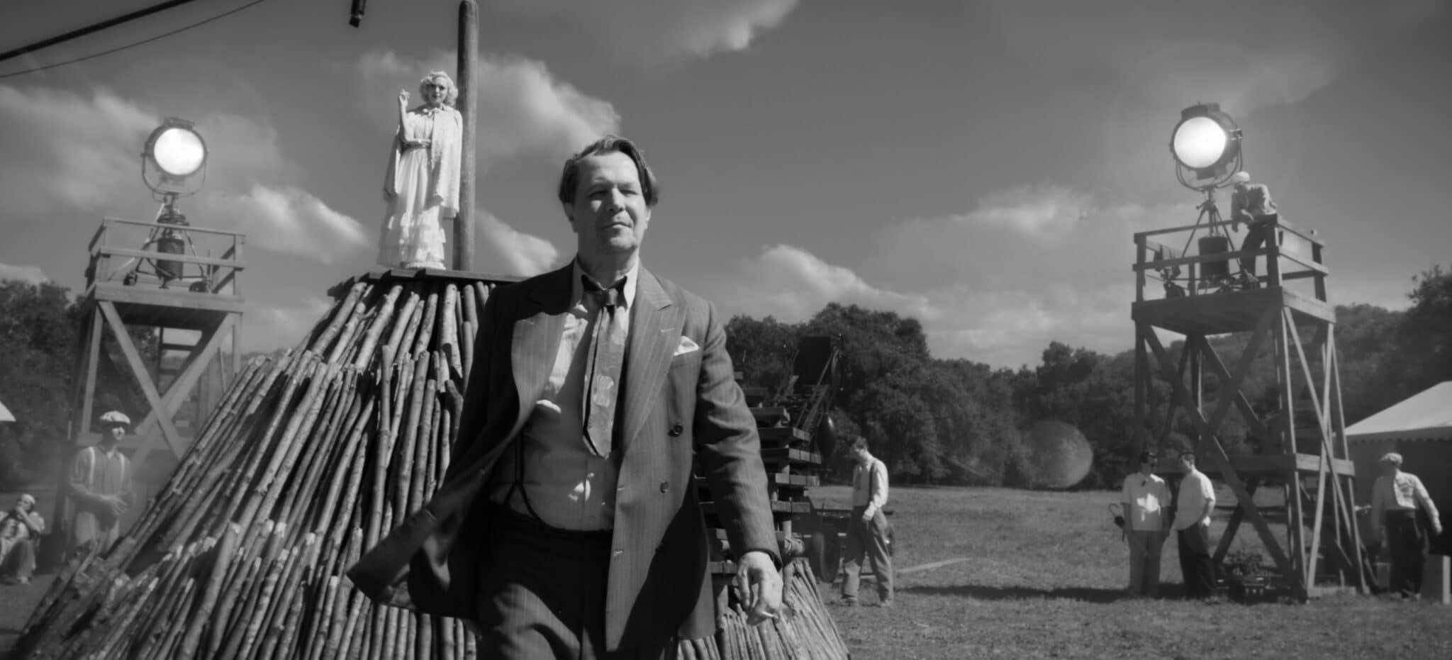 Hermann J. Mankiewicz (Gary Oldman) im Vordergrund vor einem Filmset mit Scheinwerfern und einer aufwendigen Holzkonstruktion auf der eine Dame in weißem Kleid steht.