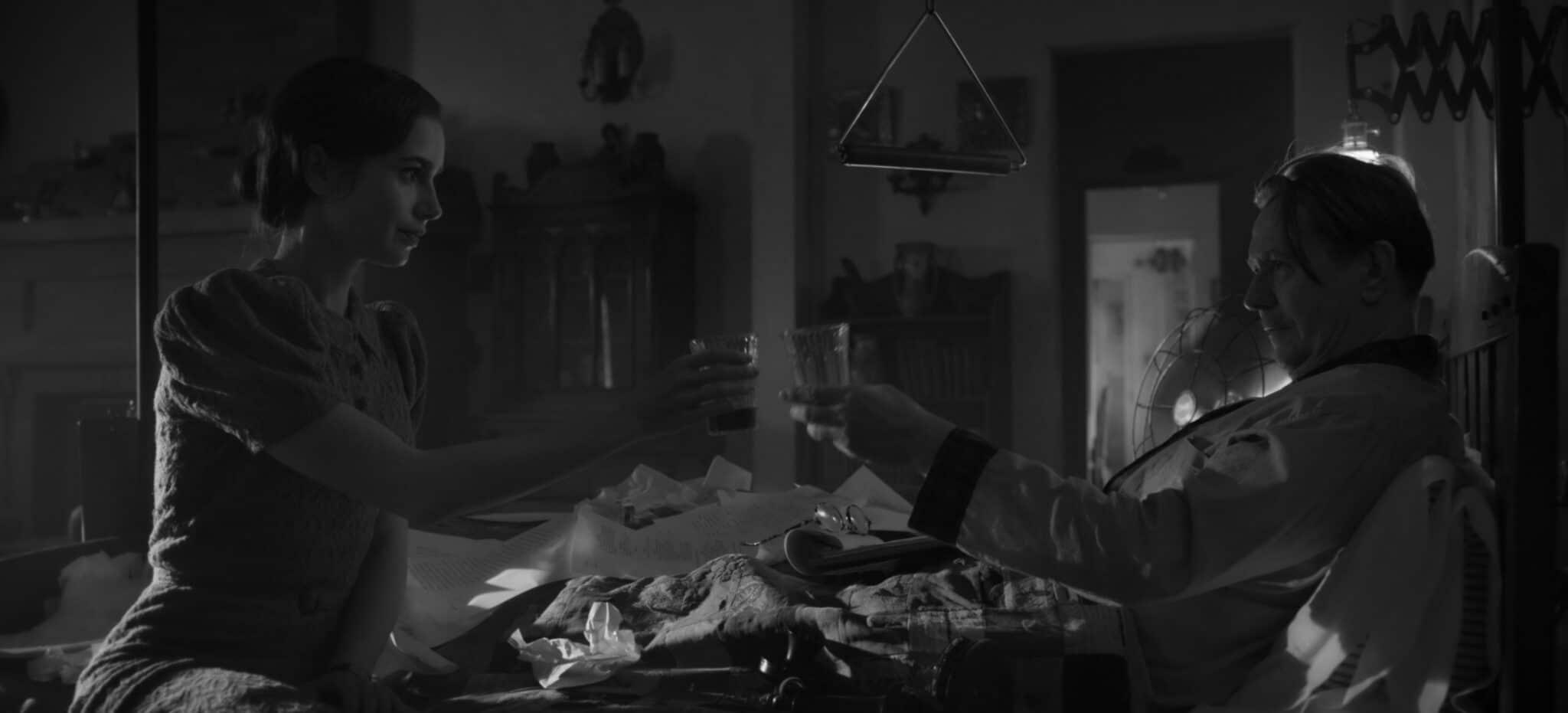 Lily Collins und Gary Oldman stoßen an, während sich Oldman in einem Krankenbett befindet.