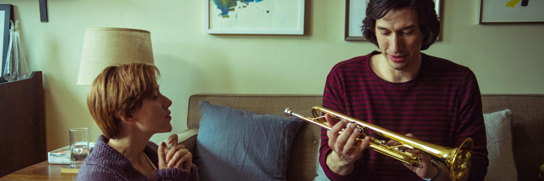 Adam Driver sitzt auf einem Sofa und hält eine trompete in den Händen, links neben ihm kniet seine Filmgattin, gespielt von Scarlett Johansson.