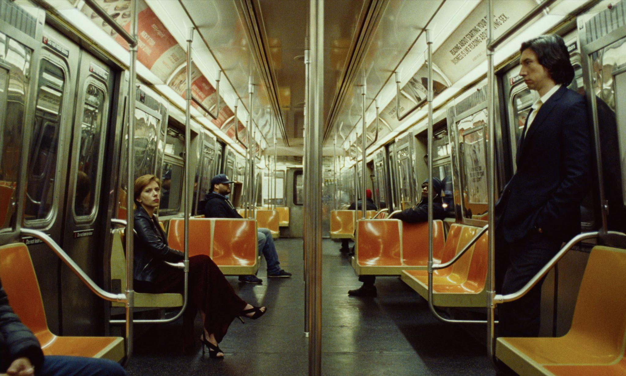 Scarlett Johansson als Nicole sitzt am linken Bildrand und Adam Driver als Charlie steht am rechten Bildrand. Die Szene spielt in einer U-Bahn.