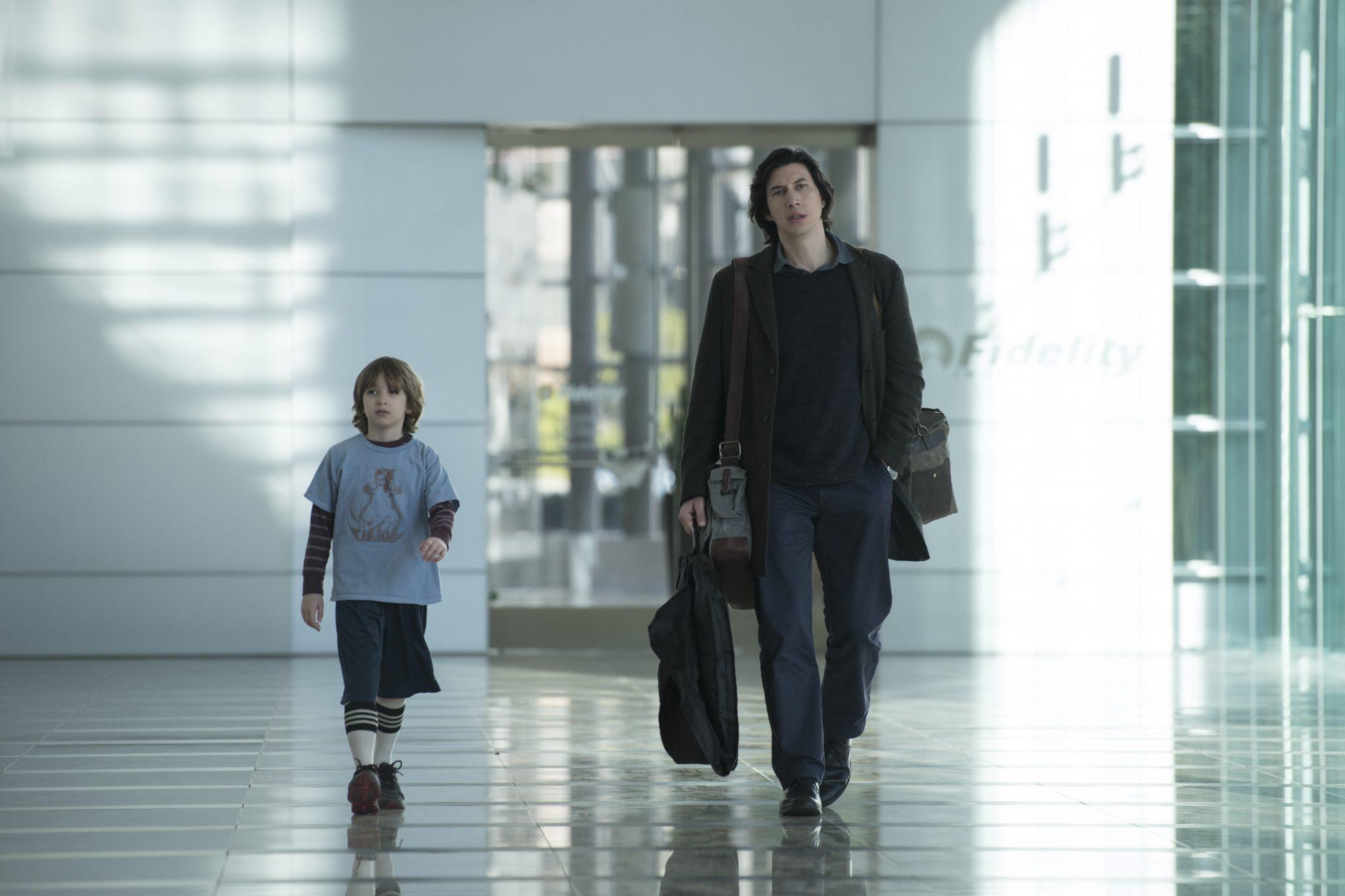 Azhy Robertson als Sohn Henry und Adam Driver als Charlie laufen in Richtung des Zuschauers und wirken dabei abgelenkt.