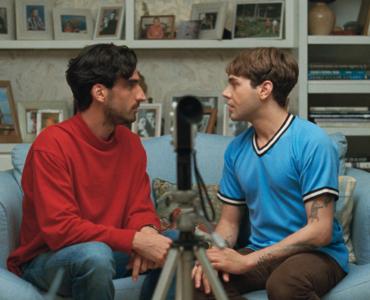 Matthias (Gabriel D'Almeida Freitas) und Maxime (Xavier Dolan) sitzen jeweils mit dem Gesicht einander zugewandt auf einer Couch, im Vordergrund steht im Mittelpunkt eine kleine Filmkamera.