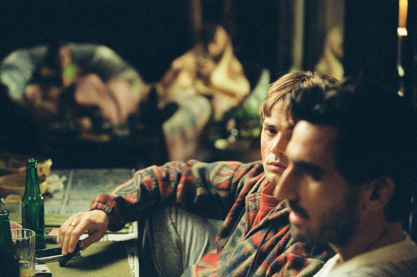 Matthias (Gabriel D'Almeida Freitas) und Maxime (Xavier Dolan) sitzen während einer Party nebeneinander. Maxime sieht Matthias von der Seite an.
