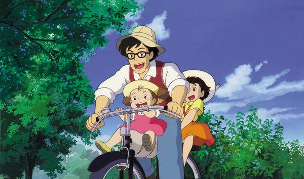 Zwei Mädchen und deren Vater fahren auf einem Fahrrad