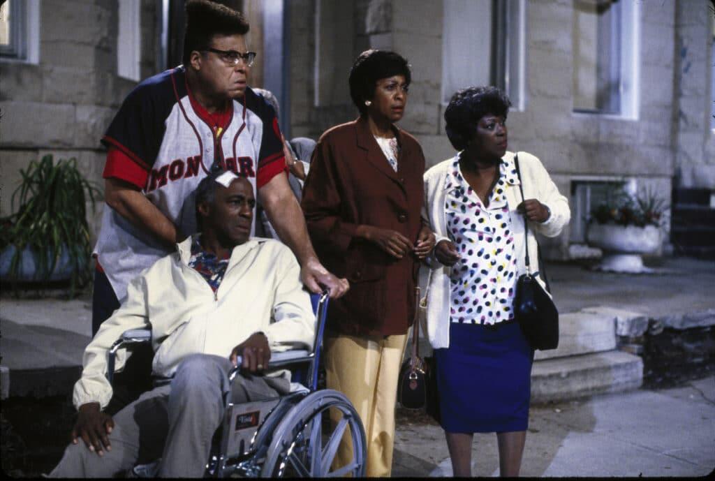 Das Bild zeigt Robert Guillaume und Maria Gibbs, die Hauptfigur Jeffersons Eltern spielen. Guillaume sitzt dabei im Rollstuhl und hat ein großes weißes Pflaster auf seinem Kopf. Der Rollstuhl wird geschoben bzw. festgehalten von Mr. Moses, den James Earl Jones spielt. Dieser trägt ein Baseball-Shirt und ein Toupet, dass einer Afro Turmfrisur ähnelt. Gemeinsam mit ihnen steht noch eine weitere Dame aus der Nachbarschaft. Alle vier machen große Augen und schauen vom Bürgersteig in Richtung Straße.
