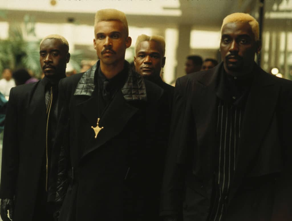 Das Bild zeigt vier Mitglieder der Golden Lords in Meteor Man. Einer von ihnen ist Don Cheadle, der ganz links im Bild ist. Alle vier tragen schwarze Kleidung und haben die Haare gelb gefärbt.