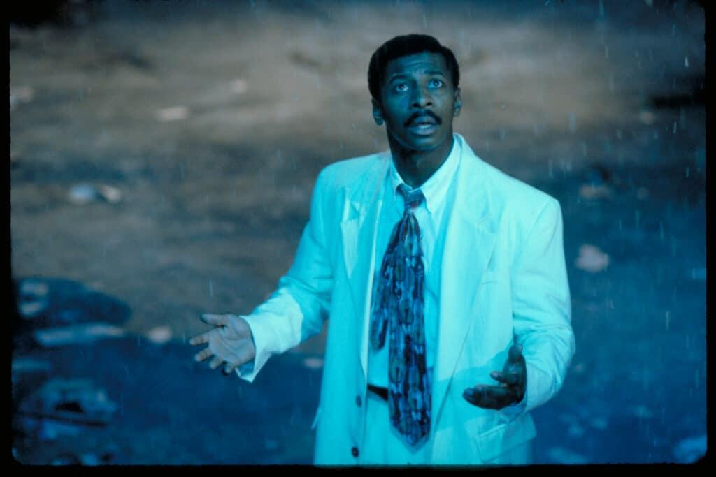 """Das Bild zeigt Jefferson Reed (Robert Townsend) in """"Meteor Man"""". Er trägt einen weißen Anzug mit bunter Krawatte. Er hat die Arme und Hände in offener Haltung als wenn er etwas mit offenen Armen erwartet hat. Sein Blick richtet sich in Richtung Himmel, wo ihn etwas türkis-grün erleuchtet."""