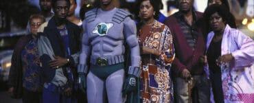Das Bild zeigt Superheld Meteor Man mit seinen Freunden und Nachbarn. Der Superheld trägt seinen grauen Heldenanzug mit grünen Applikationen und grünen Cape. Hinter ihm stehen einige Menschen und blicken ebenso wie er entsetzt auf etwas außerhalb des Bildes.