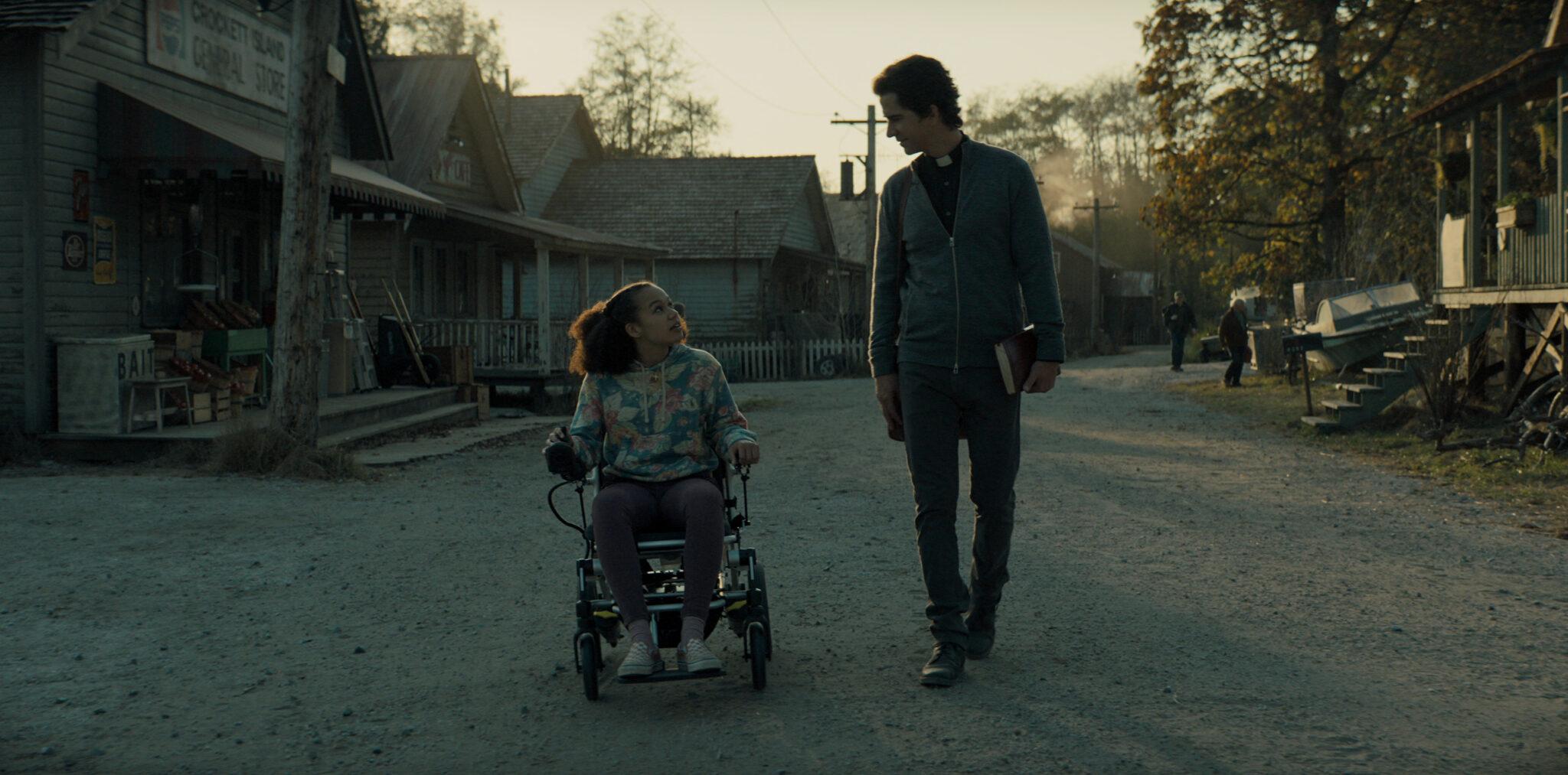 Ein Mädchen im Rollstuhl und ein Mann mit Priesterkragen und Buch im Arm bewegen sich auf einer Schotterstraße auf den Betrachter zu; im Hintergrund sieht man zahlreiche Holzhäuser - Midnight Mass