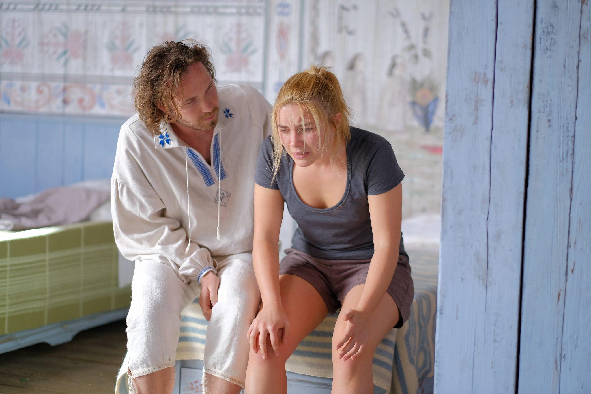 Dani (Florence Pugh) sitzt mit schmerzverzerrtem Gesicht auf der Bettkante, ein junger Mann im altertümlichen Gewand spendet Trost. Szenenbild aus Midsommar, einem der besten A24-Filme.