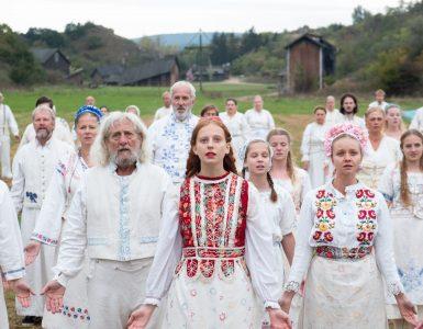 In einem Szenenbild aus Midsommar starren ein paar festlich gekleidete Sektenanhänger direkt in die Kamera.