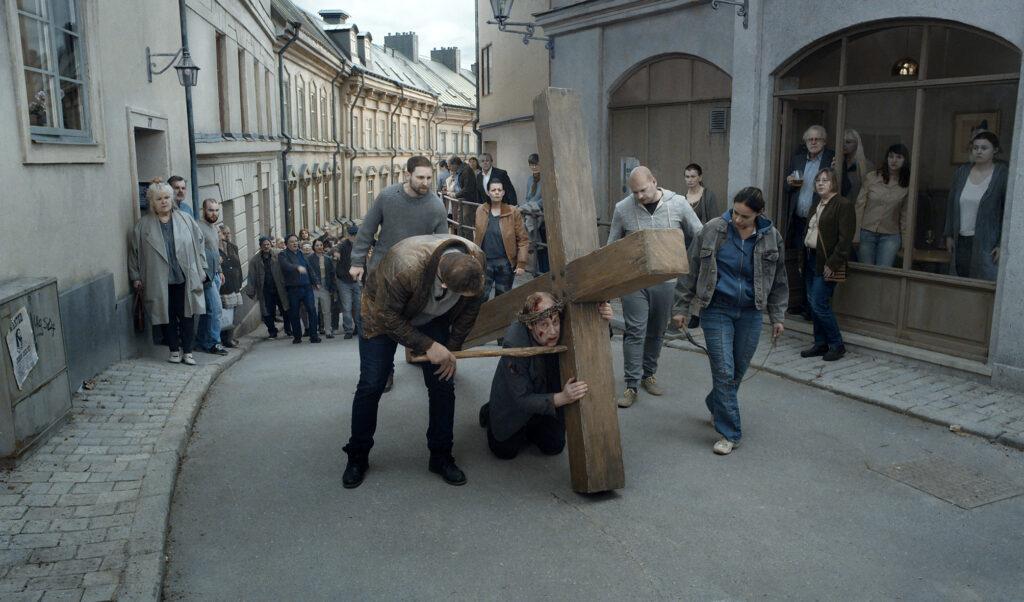 In Über die Unendlichkeit schleppt ein entkräfteter Mann ein großes Holzkreuz durch die Straßen etliche Menschen begleiten und folgen ihm dabei.