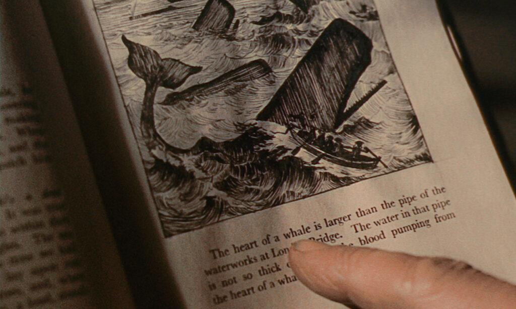 Zu sehen ist die Beschreibung eines Wales in einem alten Buch von Queequeg, die dieser mitsamt seines Zeigefingers zu Lesen versucht.