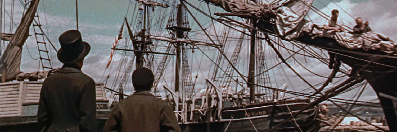 Die beiden Figuren Queequeg und Ismael sind von links nach rechts in der linken, unteren Bildecke und blicken auf das Segelschiff, auf dem sie bald anheuern. Ihre Rücken haben sie dabei zum Publikum zugewandt. Moby Dick - © Capelight Pictures
