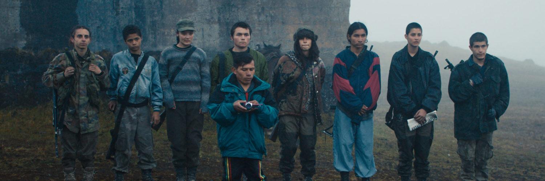 Der kleinwüchsige Ausbilder steht in Monos - Zwischen Himmel und Hölle mit einem Camcorder vor den aufgereihten Soldaten bestehend aus Teenagern.