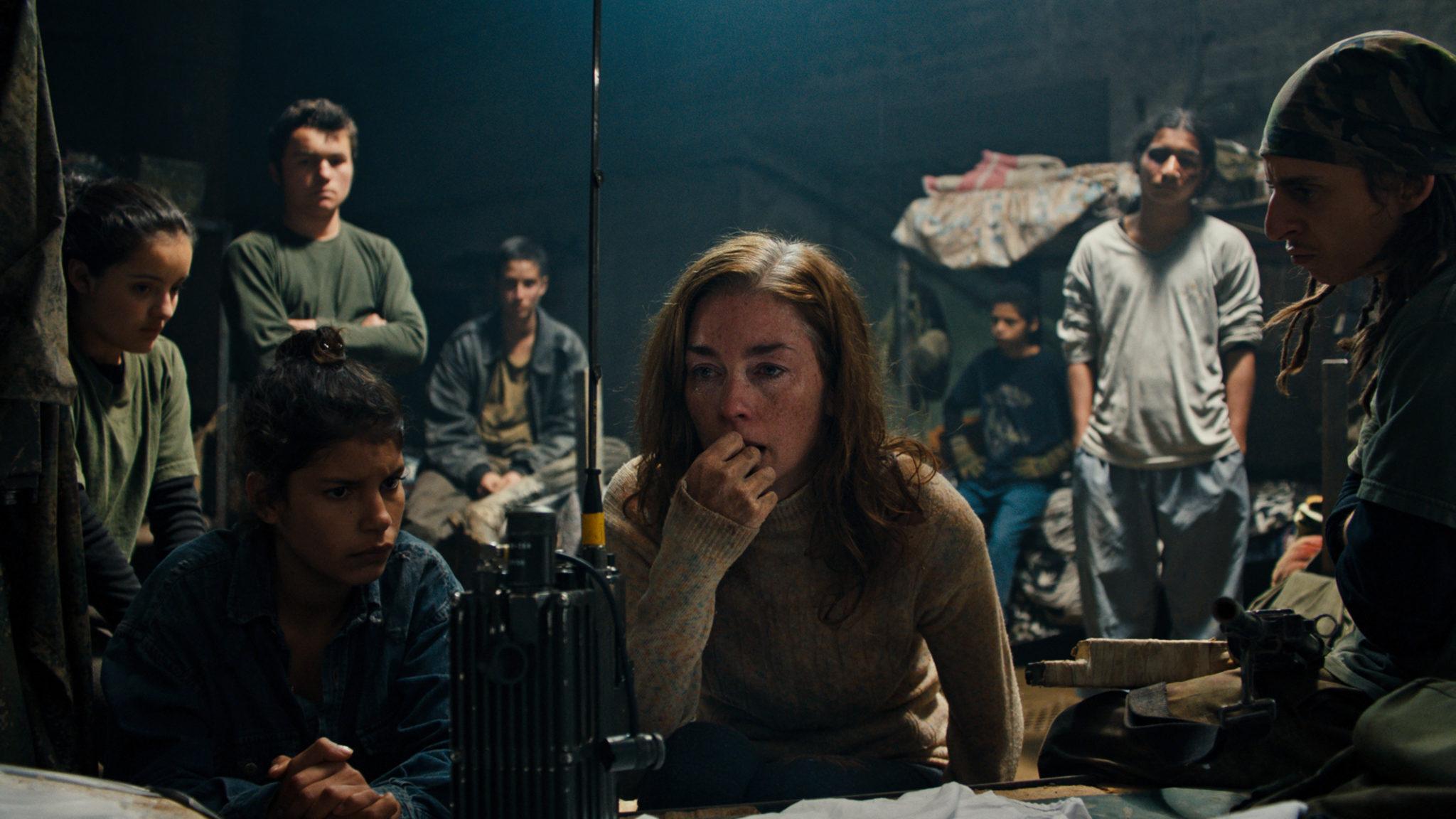 Die Doctora sitzt in Monos - Zwischen Himmel und Hölle verzweifelt vor einem Funkgerät. Die Rebellentruppe versammelt sich um sie herum.