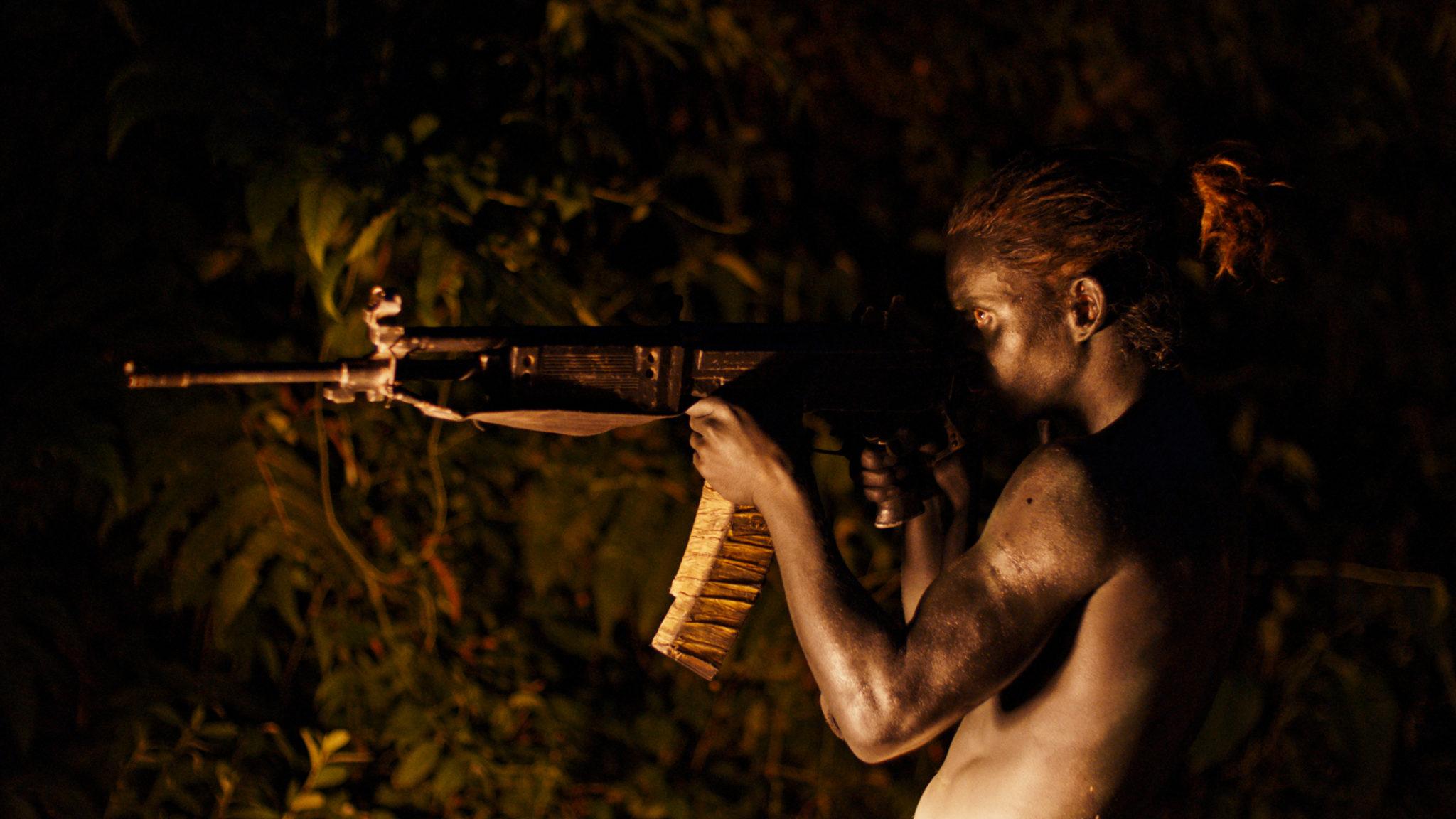 Bigfoot (Moisés Arias) steht in Monos - Zwischen Himmel und Hölle nachts, von gelbem Licht angeleuchtet zielend mit dem Sturmgewehr im Dschungel.