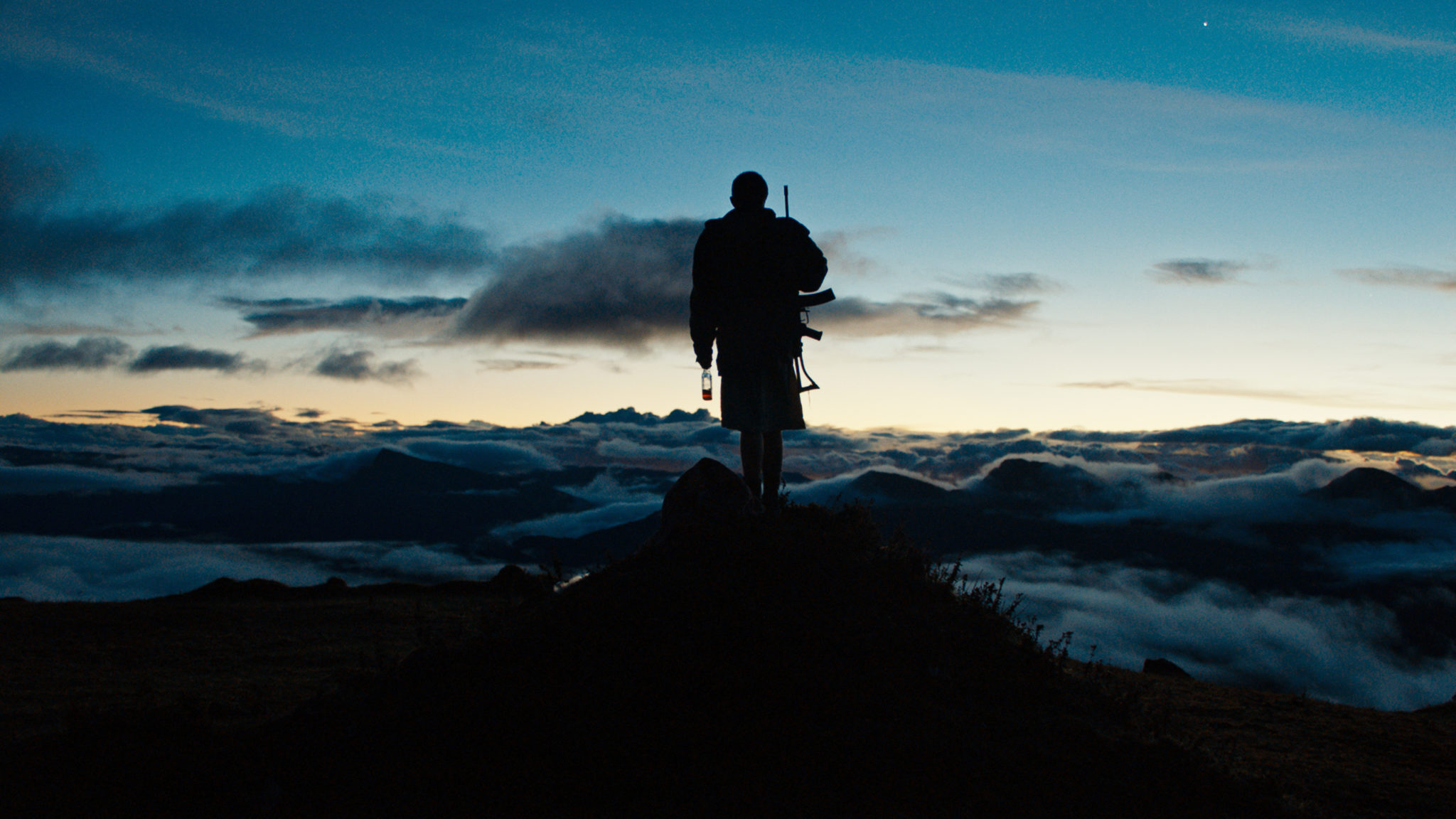 Im Vordergrund sehen wir schemenhaft einen der (Kinder-)Soldaten stehen, Waffe und Schnaps in den Händen. Im Hintergrund erstreckt sich die schöne Berglandschaft bei Sonnenuntergang in Monos - Zwischen Himmel und Hölle.