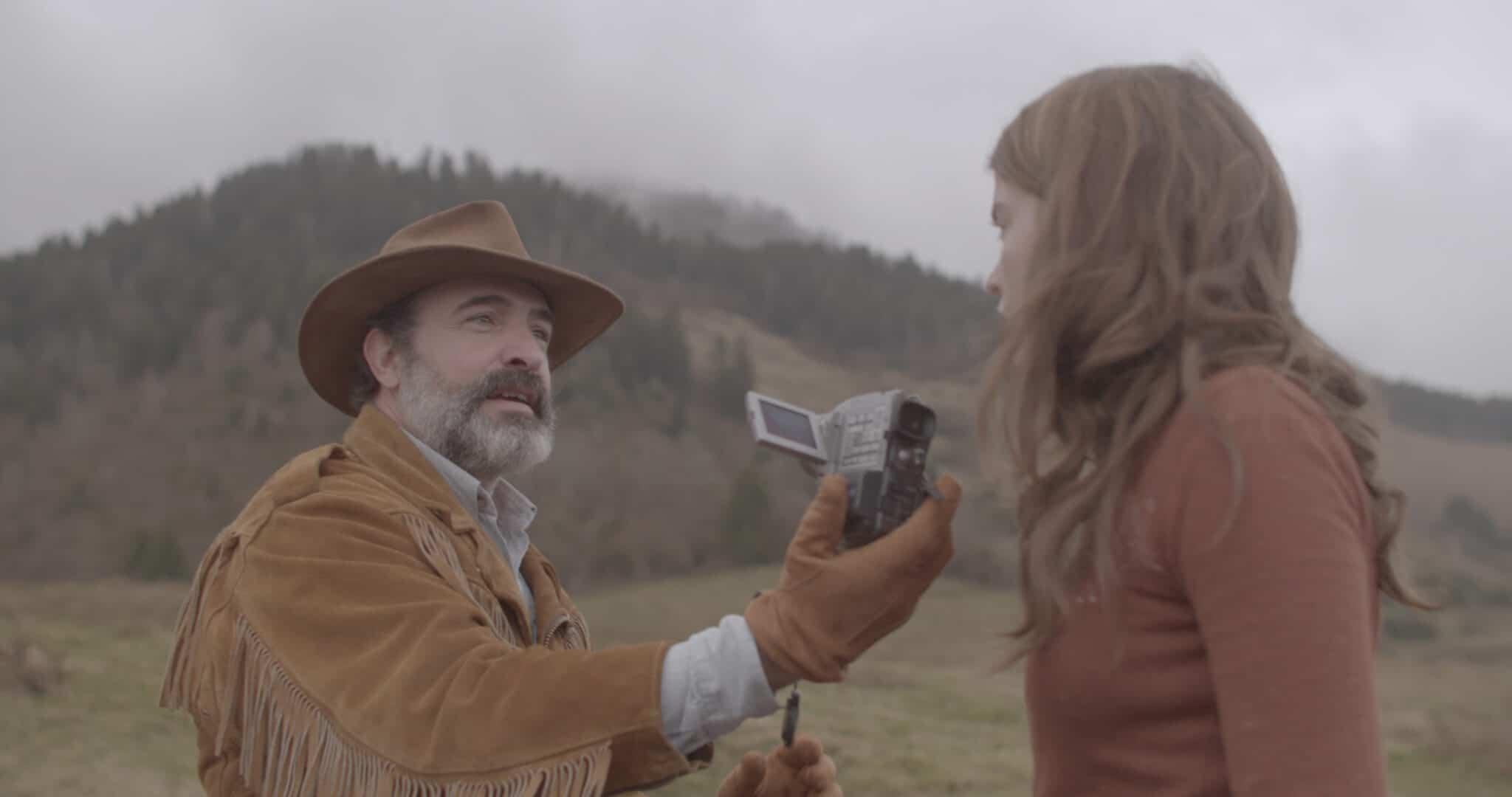 In Monsieur Killerstyle fordert Georges (Jean Dujardin) Denise (Adèle Haenel) auf, ihn zu filmen. Er ist inzwischen in voller Wildledermontur, bestehend aus Jacke, Hut, Handschuhen, Hose und Stiefeln. Denise sieht etwas verwirrt aus. Im Hintergrund ist eine vernebelte Hügellandschaft zu sehen.